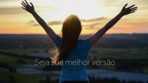 Imagem mulher de costas a ver o pôr do sol com os braços abertos em expressão de liberdade