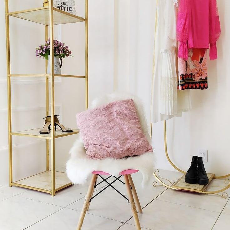 Cadeira branca no centro da imagem com almofada rosa de pelo. Cabide com algumas roupas nos mesmos tons.